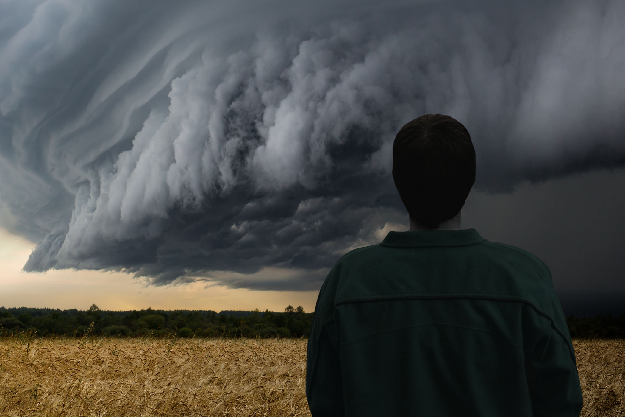 A mean looking huge storm cloud hovering over a field